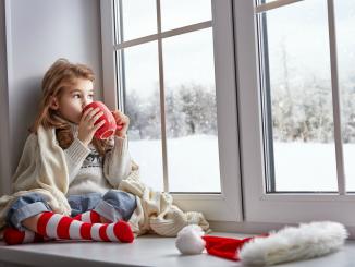 Девочка с чашкой чая у окна в преддверии Нового Года