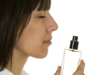 Женщина нюхает запах духов