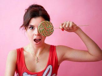 Молодая девушка с большой конфетой в руке