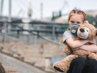 Девочка в маске с плюшевым мишкой